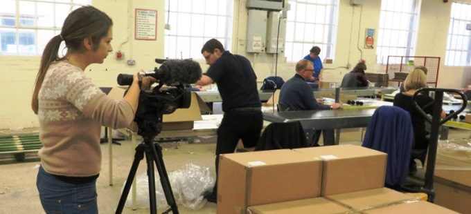 BBC reporter Frankie Peck films staff working on the shopfloor at Enham Packaging & Storage